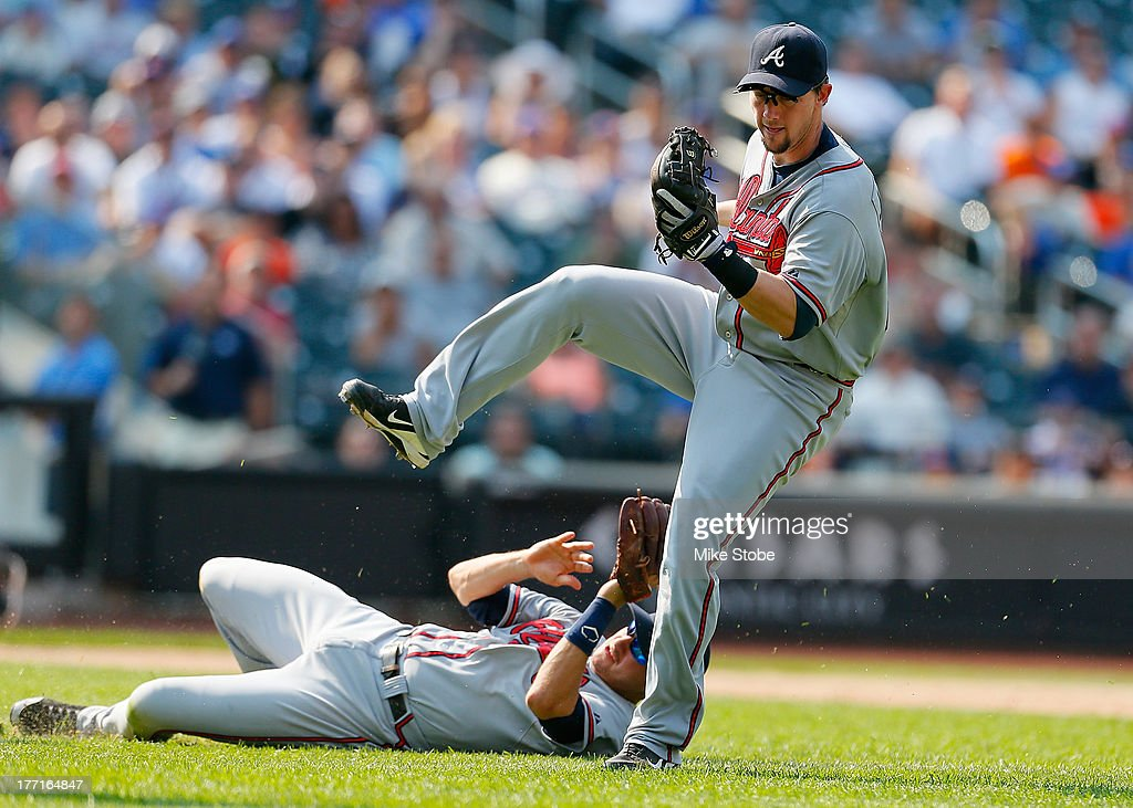 Chris Johnson #23 of the Atlanta Braves leaps over <a gi-track='captionPersonalityLinkClicked' href=/galleries/search?phrase=Paul+Janish&family=editorial&specificpeople=4174475 ng-click='$event.stopPropagation()'>Paul Janish</a> #4 catching a pop up against the New York Mets at Citi Field on August 21, 2013 at Citi Field in the Flushing neighborhood of the Queens borough of New York City. Braves defeated the Mets 4-1.