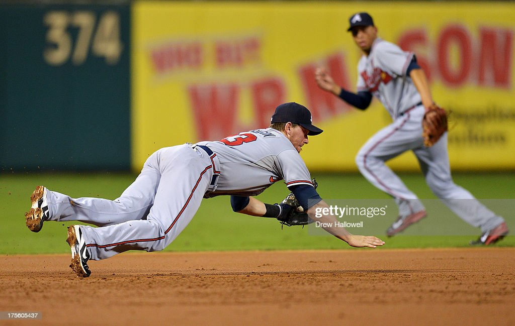 Chris Johnson #23 of the Atlanta Braves makes a diving catch on a ground ball in the first inning against the Philadelphia Phillies as Andrelton Simmons #19 runs to backup at Citizens Bank Park on August 4, 2013 in Philadelphia, Pennsylvania.