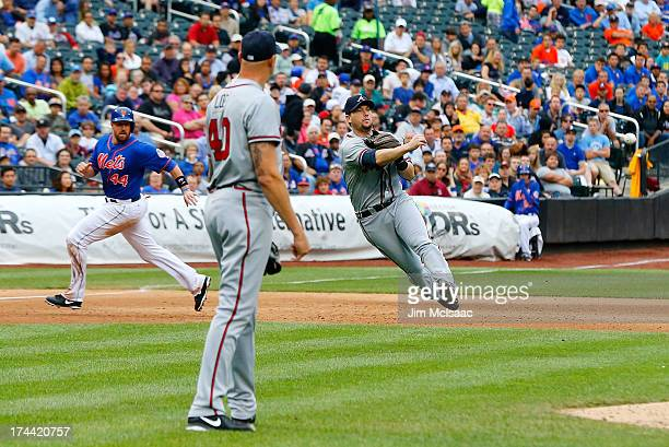 Chris Johnson of the Atlanta Braves throws to first base for the final out of the sixth inning as teammate Kameron Loe and John Buck of the New York...