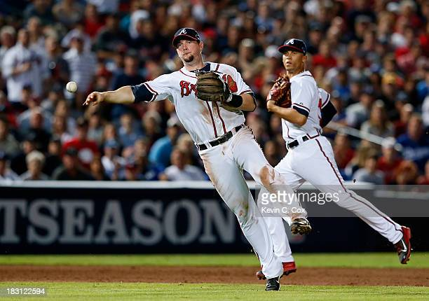 Chris Johnson of the Atlanta Braves tries to throw out Yasiel Puig of the Los Angeles Dodgers in the sixth inning during Game Two of the National...