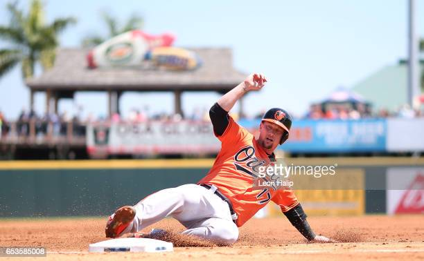 Chris Johnson of the Baltimore Orioles slides into third base during the second inning of a spring training game against the Pittsburgh Pirates on...