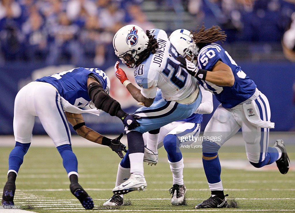 Chris Johnson of the Tennessee Titans is tackled by Antoine Bethea and Philip Weaver of the Indianapolis Colts at Lucas Oil Stadium on December 6...
