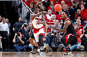 Chris Jones of the Louisville Cardinals passes the ball while defended by Anthony Barber of the North Carolina State Wolfpack during the game at KFC...