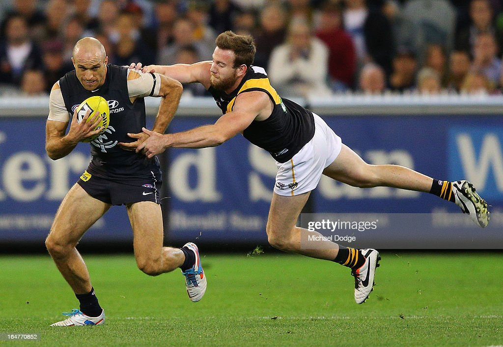 A Chris Judd of the Blues runs with the ball past Jake Batchelor of the Tigers during the round one AFL match between the Carlton Blues and the Richmond Tigers at Melbourne Cricket Ground on March 28, 2013 in Melbourne, Australia.