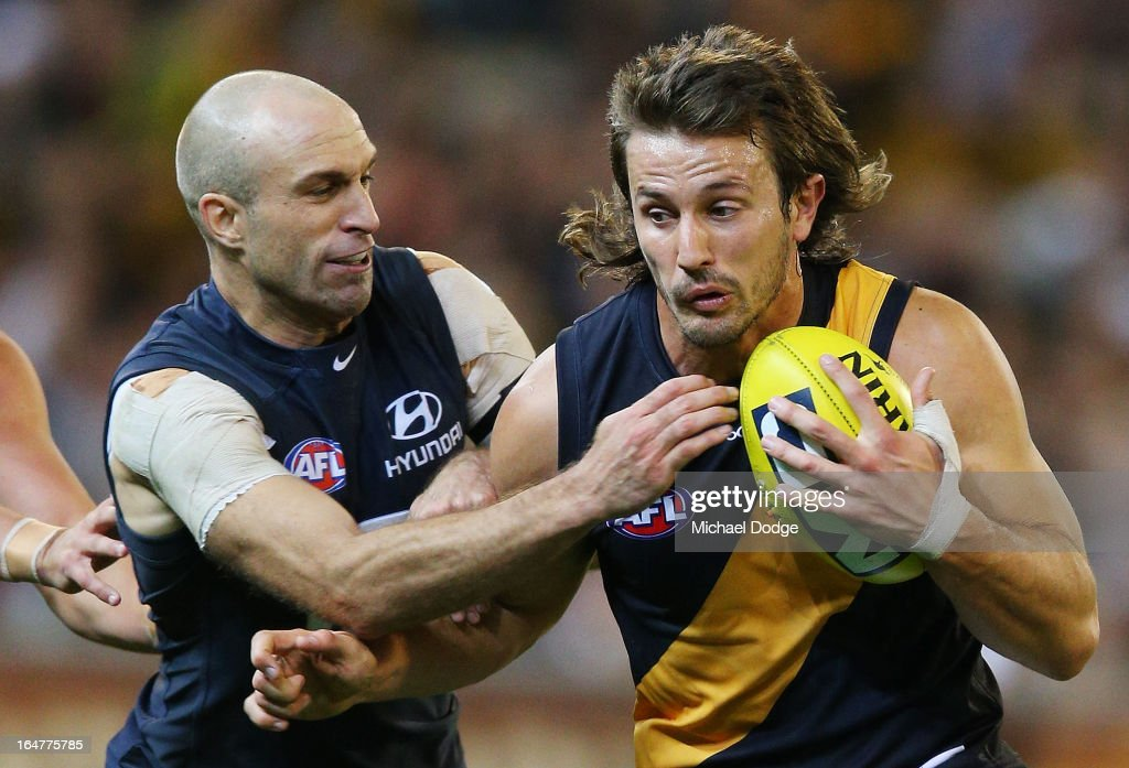 A Chris Judd of the Blues tackles Ivan Maric of the Tigers during the round one AFL match between the Carlton Blues and the Richmond Tigers at Melbourne Cricket Ground on March 28, 2013 in Melbourne, Australia.