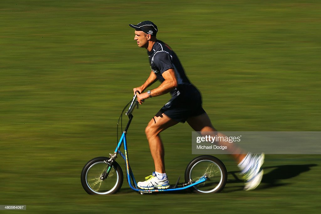 Chris Judd pushes a scooter to rehabilitate his archilles during a Carlton Blues training session at Visy Park on March 26, 2014 in Melbourne, Australia.