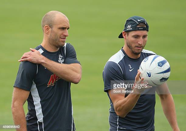 Chris Judd touches his shoulder as Dale Thomas holds a soccer ball during a Carlton Blues AFL preseason training session at Visy Park on November 29...