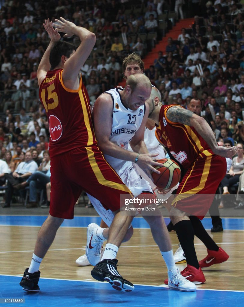 Chris Kaman (C) of Germany drives against Predrag Samardjiski (L) and Pero Antic of Macedonia during a international Basketball Friendly between Germany and Macedonia on August 26, 2011 in Munich, Germany.