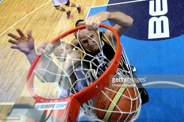 Chris Kaman of Germany dunks the ball against Mareks Mejeris of Latvia during the EuroBasket 2011 first round group B match between Latvia and...