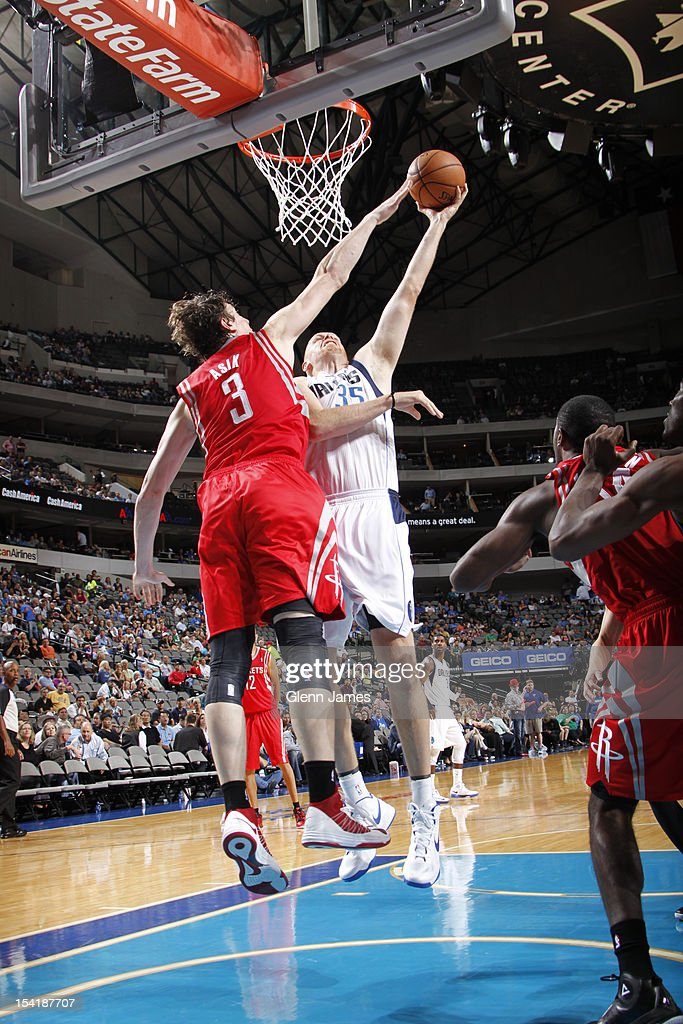 Chris Kaman #35 of the Dallas Mavericks goes in for the layup against Omer Asik #3 of the Houston Rockets on October 15, 2012 at the American Airlines Center in Dallas, Texas.
