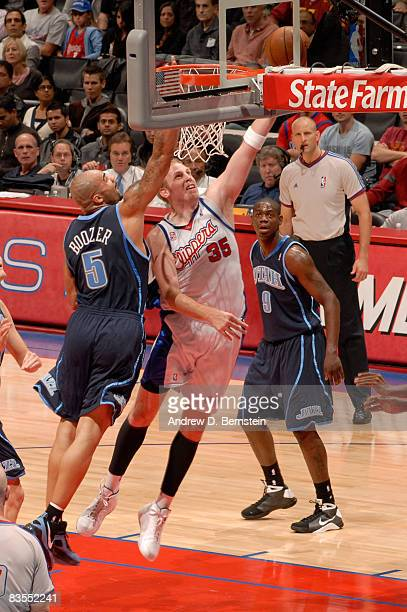 Chris Kaman of the Los Angeles Clippers puts up a shot against Carlos Boozer of the Utah Jazz at Staples Center on November 3 2008 in Los Angeles...