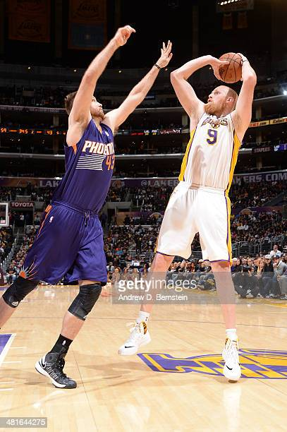 Chris Kaman of the Los Angeles Lakers shoots against Shavlik Randolph of the Phoenix Suns at STAPLES Center on March 30 2014 in Los Angeles...