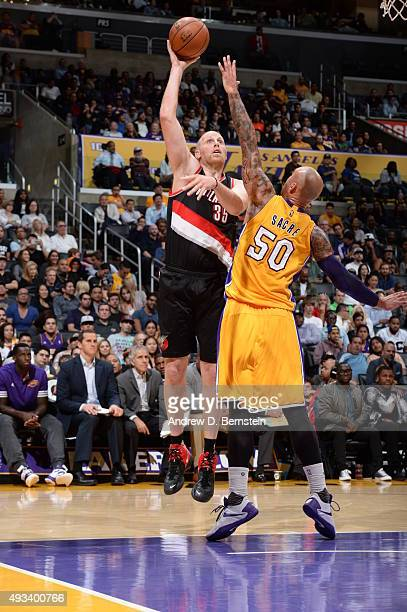 Chris Kaman of the Portland Trail Blazers shoots against Robert Sacre of the Los Angeles Lakers during the preseason game on October 19 2015 at...