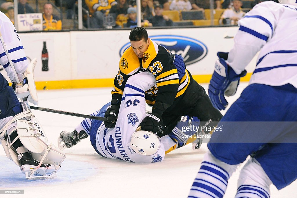 Chris Kelly #23 of the Boston Bruins falls on top of <a gi-track='captionPersonalityLinkClicked' href=/galleries/search?phrase=Carl+Gunnarsson&family=editorial&specificpeople=5557315 ng-click='$event.stopPropagation()'>Carl Gunnarsson</a> #36 of the Toronto Maple Leafs in Game Two of the Eastern Conference Quarterfinals during the 2013 NHL Stanley Cup Playoffs at TD Garden on May 4, 2013 in Boston, Massachusetts.