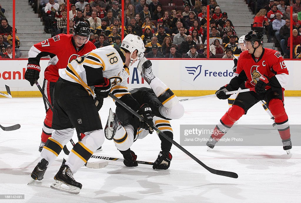 Chris Kelly of the Boston Bruins falls to the ice as teammate Reilly Smith and Derek Grant and Jason Spezza of the Ottawa Senators look on during an...