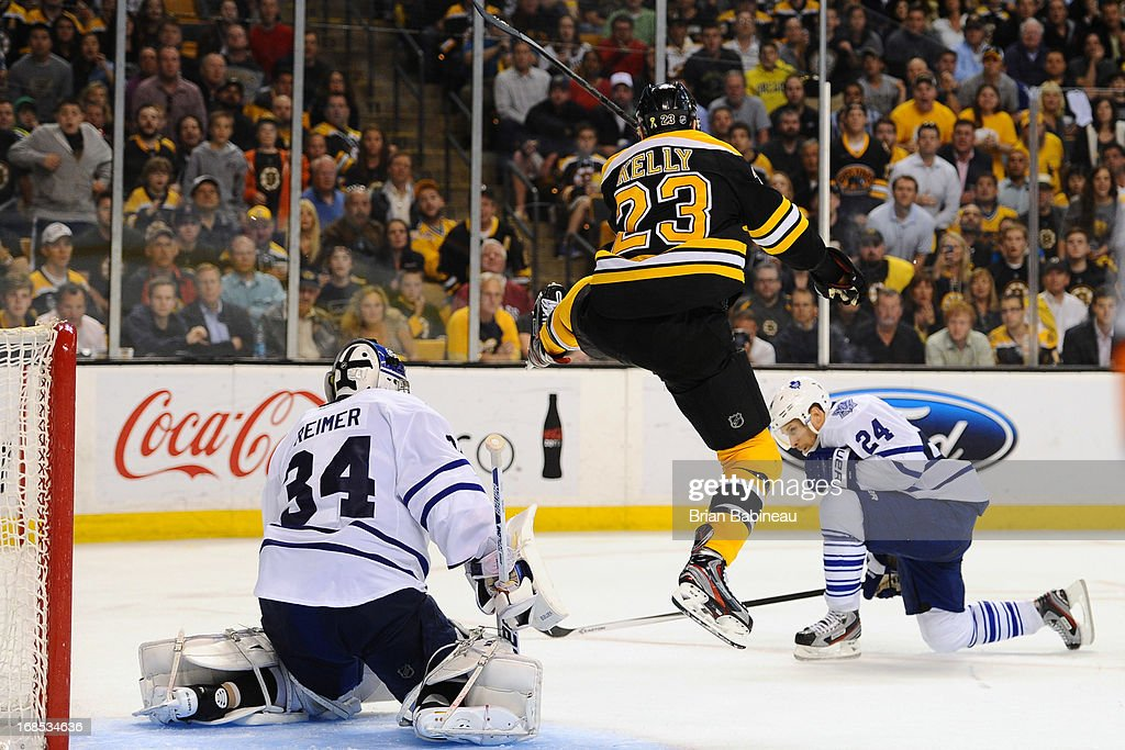 Chris Kelly #23 of the Boston Bruins hops up in the air to avoid the puck against James Reimer #34 and <a gi-track='captionPersonalityLinkClicked' href=/galleries/search?phrase=John-Michael+Liles&family=editorial&specificpeople=206866 ng-click='$event.stopPropagation()'>John-Michael Liles</a> #24 of the Toronto Maple Leafs in Game Five of the Eastern Conference Quarterfinals during the 2013 NHL Stanley Cup Playoffs at TD Garden on May 10, 2013 in Boston, Massachusetts.