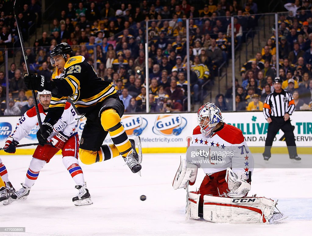 Chris Kelly #23 of the Boston Bruins jumps in front of a loose puck in front of <a gi-track='captionPersonalityLinkClicked' href=/galleries/search?phrase=Braden+Holtby&family=editorial&specificpeople=5370964 ng-click='$event.stopPropagation()'>Braden Holtby</a> #70 of the Washington Capitals in the third period during the game at TD Garden on March 6, 2014 in Boston, Massachusetts.