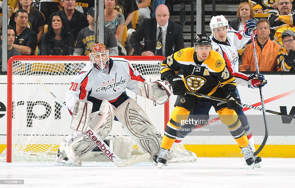 Chris Kelly #23 of the Boston Bruins watches the play against Braden Holtby #70 and Jay Beagle #83 of the Washington Capitals in Game Five of the Eastern Conference Quarterfinals during the 2012 NHL Stanley Cup Playoffs at TD Garden on April 21, 2012 in Boston, Massachusetts.