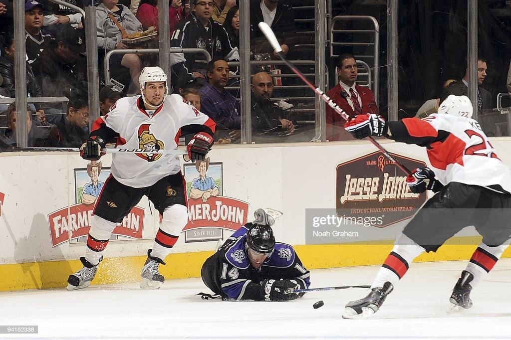 Chris Kelly of the Ottawa Senators grabs the puck as Justin Williams of the Los Angeles Kings falls to the ice defending the puck during the game on...