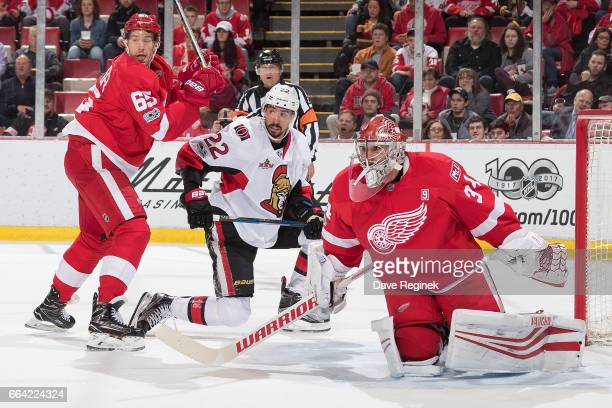 Chris Kelly of the Ottawa Senators skates in front of the net while being defended by Danny DeKeyser of the Detroit Red Wings as teammate goaltender...