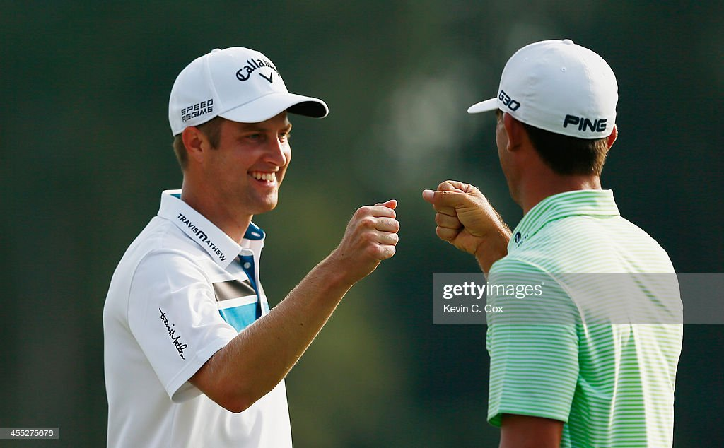 Chris Kirk and Billy Horschel of the United States react to Kirk's birdie on the 17th hole during the first round of the TOUR Championship by...