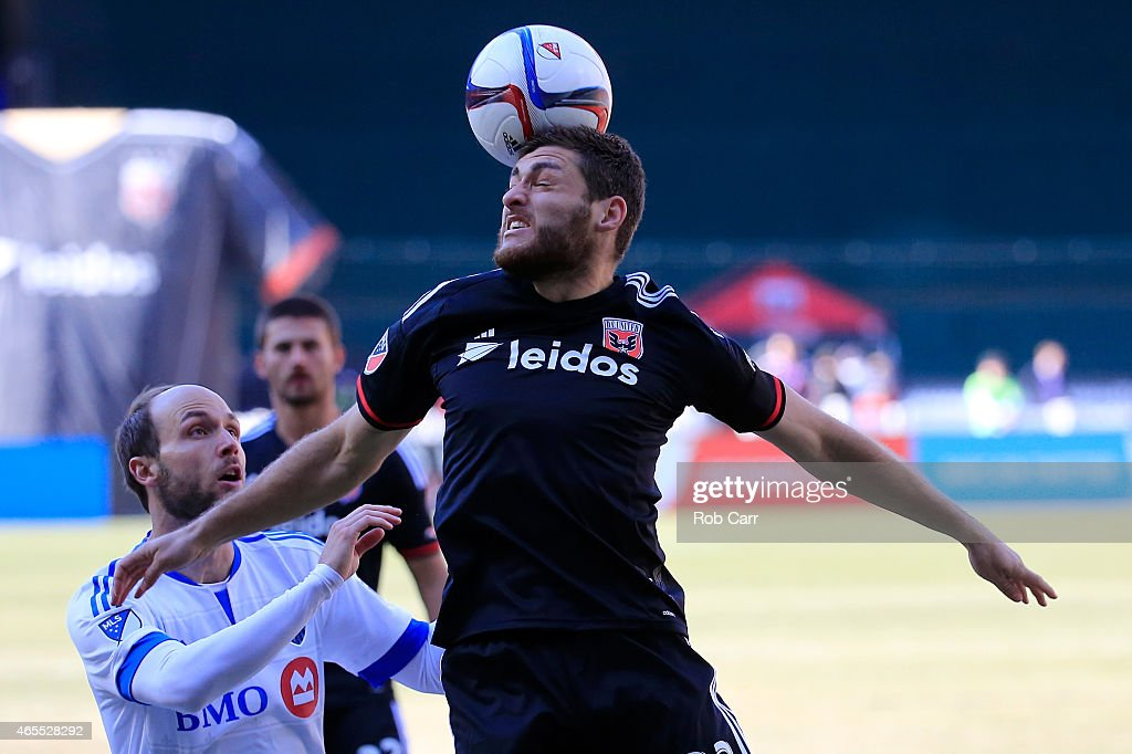 Chris Korb of DC United heads the ball in front of Justin Mapp of Montreal Impact during the first half at RFK Stadium on March 7 2015 in Washington...