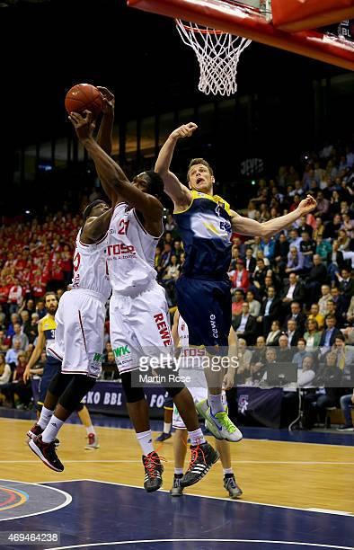 Chris Kramer of Oldenburg challenges Trevor Mbakwe of Bamberg for the ball during the BEKO BBL Top Four final game between EWE Baskets Oldenburg and...