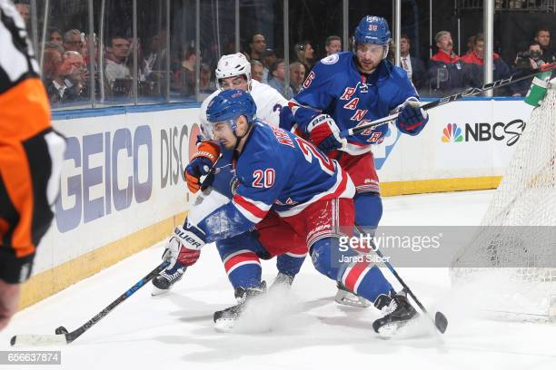 Chris Kreider and Mats Zuccarello of the New York Rangers battle for the puck against Travis Hamonic of the New York Islanders at Madison Square...