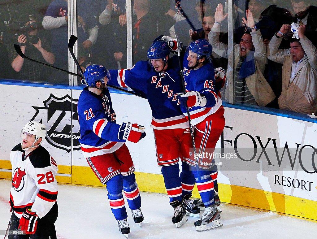 Chris Kreider celebrates his third period goal with teammates Artem Anisimov and Derek Stepan of the New York Rangers as Anton Volchenkov of the New...
