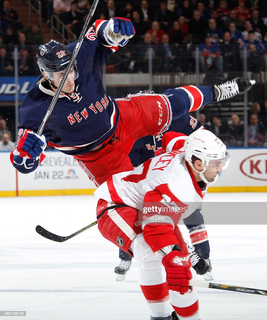 Chris Kreider #20 of the New York Rangers is hit by Kyle Quincey #27 of the Detroit Red Wings at Madison Square Garden on January 16, 2014 in New York City.