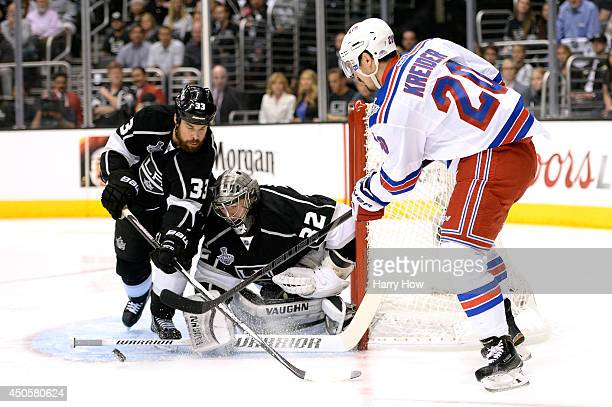 Chris Kreider of the New York Rangers looks to shoot in front of the net against Willie Mitchell and goaltender Jonathan Quick of the Los Angeles...