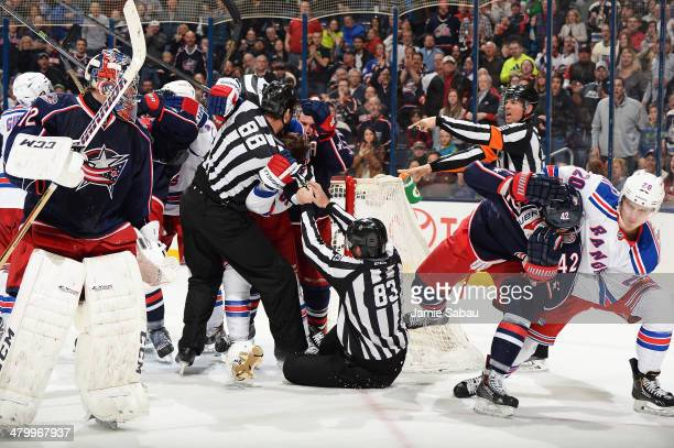 Chris Kreider of the New York Rangers pulls Artem Anisimov of the Columbus Blue Jackets away as linesmen Mike Cvik and Matt MacPherson attempt to...