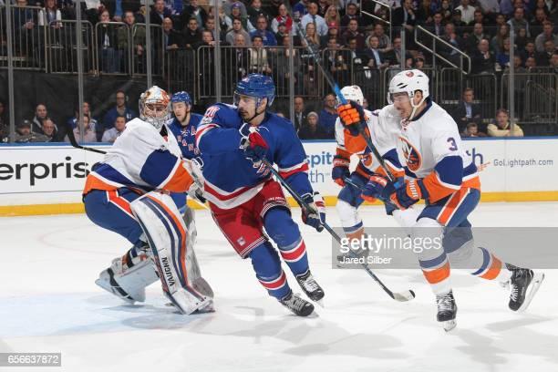 Chris Kreider of the New York Rangers skates against Thomas Greiss and Travis Hamonic of the New York Islanders at Madison Square Garden on March 22...