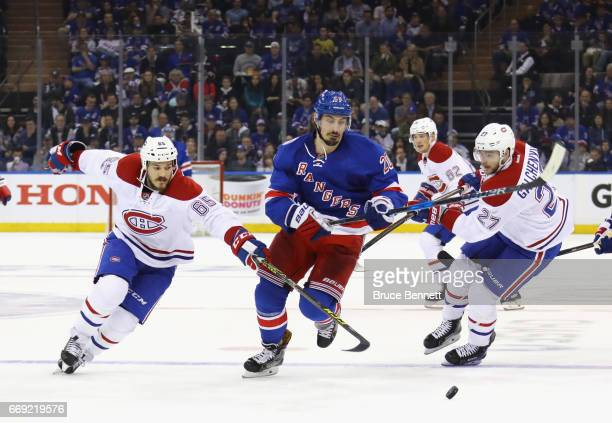 Chris Kreider of the New York Rangers skates away from Andrew Shaw and Alex Galchenyuk of the Montreal Canadiens in Game Three of the Eastern...
