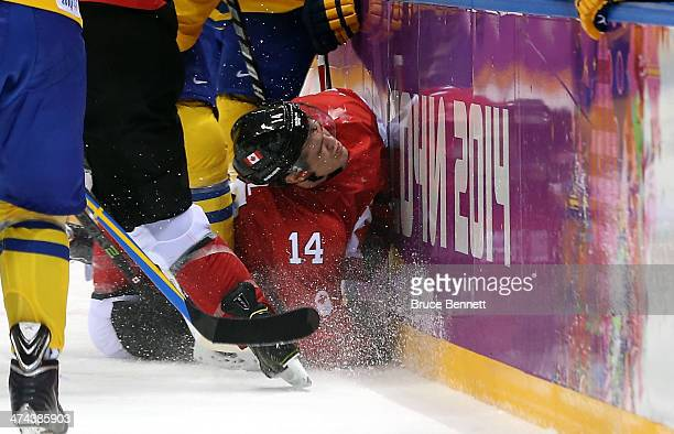 Chris Kunitz of Canada crashes into the boards during the Men's Ice Hockey Gold Medal match against Sweden on Day 16 of the 2014 Sochi Winter...
