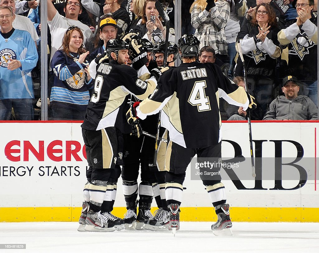 Chris Kunitz #14 of the Pittsburgh Penguins celebrates his hat trick goal with Pascal Dupuis #9 and Mark Eaton #4 during the second period against the New York Islanders on March 10, 2013 at Consol Energy Center in Pittsburgh, Pennsylvania.