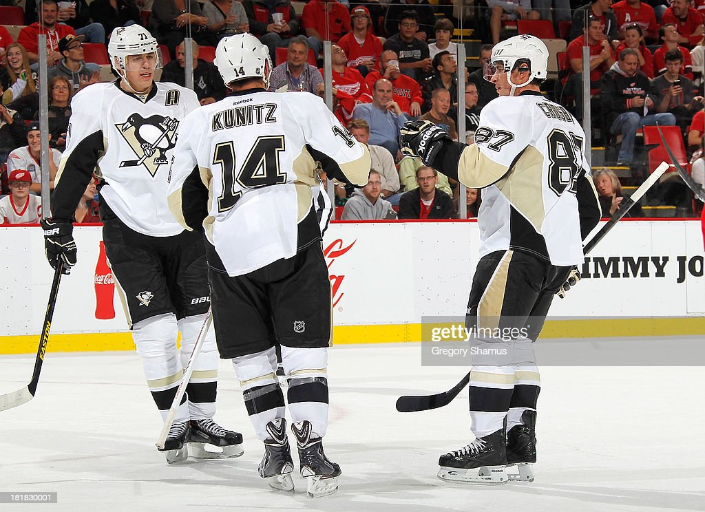 <a gi-track='captionPersonalityLinkClicked' href=/galleries/search?phrase=Chris+Kunitz&family=editorial&specificpeople=604159 ng-click='$event.stopPropagation()'>Chris Kunitz</a> #14 of the Pittsburgh Penguins celebrates his third period goal with <a gi-track='captionPersonalityLinkClicked' href=/galleries/search?phrase=Evgeni+Malkin&family=editorial&specificpeople=221676 ng-click='$event.stopPropagation()'>Evgeni Malkin</a> #71 and <a gi-track='captionPersonalityLinkClicked' href=/galleries/search?phrase=Sidney+Crosby&family=editorial&specificpeople=212781 ng-click='$event.stopPropagation()'>Sidney Crosby</a> #87 while playing the Detroit Red Wings during a pre season game at Joe Louis Arena on September 25, 2013 in Detroit, Michigan. The Penguins won the game 5-1.