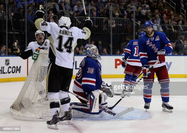 Chris Kunitz of the Pittsburgh Penguins celebrates his third period goal with teammate Sidney Crosby as Henrik Lundqvist and Dan Girardi of the New...