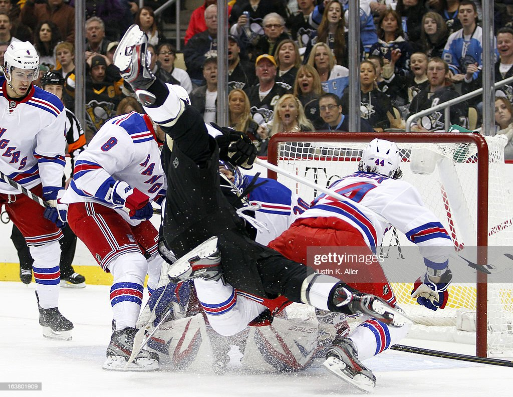 Chris Kunitz of the Pittsburgh Penguins is up ended by Steve Eminger of the New York Rangers during the game at Consol Energy Center on March 16 2013...