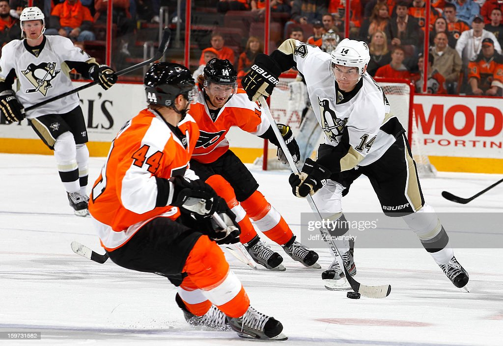 Chris Kunitz #14 of the Pittsburgh Penguins moves the puck by Sean Couturier #14 of the Philadelphia Flyers at Wells Fargo Center on January 19, 2013 in Philadelphia, Pennsylvania.
