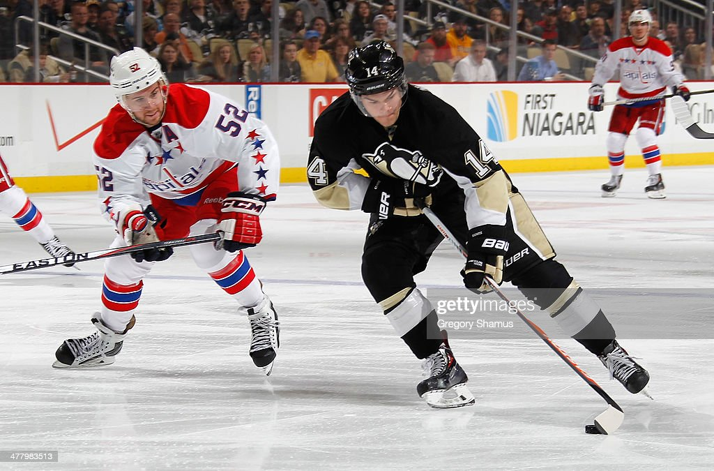 <a gi-track='captionPersonalityLinkClicked' href=/galleries/search?phrase=Chris+Kunitz&family=editorial&specificpeople=604159 ng-click='$event.stopPropagation()'>Chris Kunitz</a> #14 of the Pittsburgh Penguins moves the puck past the defense of Mike Green #52 of the Washington Capitals on March 11, 2014 at Consol Energy Center in Pittsburgh, Pennsylvania.