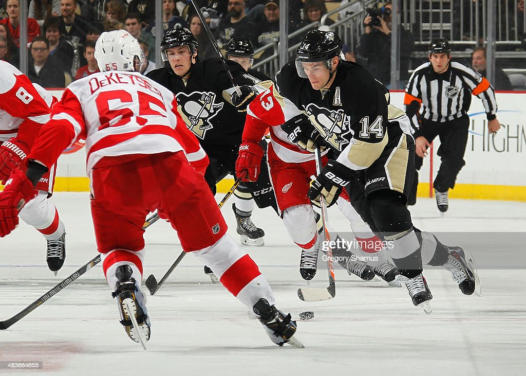 Chris Kunitz #14 of the Pittsburgh Penguins moves the puck up ice in front of Danny DeKeyser #65 of the Detroit Red Wings on April 9, 2014 at Consol Energy Center in Pittsburgh, Pennsylvania.