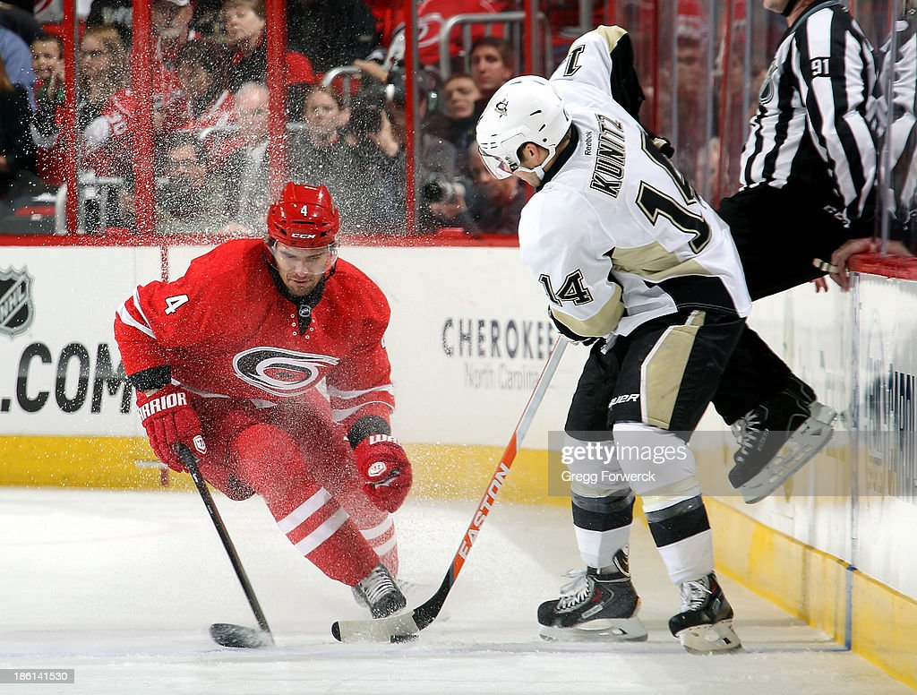 Chris Kunitz #14 of the Pittsburgh Penguins pulls the puck away from an approacing Andrej Sekera #4 of the Carolina Hurricanes during their NHL game at PNC Arena on October 28, 2013 in Raleigh, North Carolina.