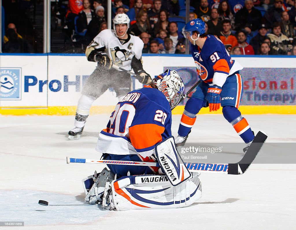 Chris Kunitz #14 of the Pittsburgh Penguins (not pictured) shoots the puck past Evgeni Nabokov #20 of the New York Islanders for a second-period goal at 19:46 in an NHL hockey game at Nassau Veterans Memorial Coliseum on March 22, 2013 in Uniondale, New York.