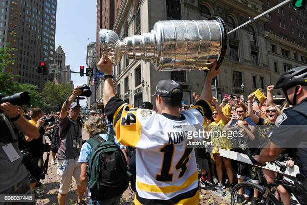 Chris Kunitz of the Pittsburgh Penguins walks the Stanley Cup along the route during the Victory Parade and Rally on June 14 2017 in Pittsburgh...