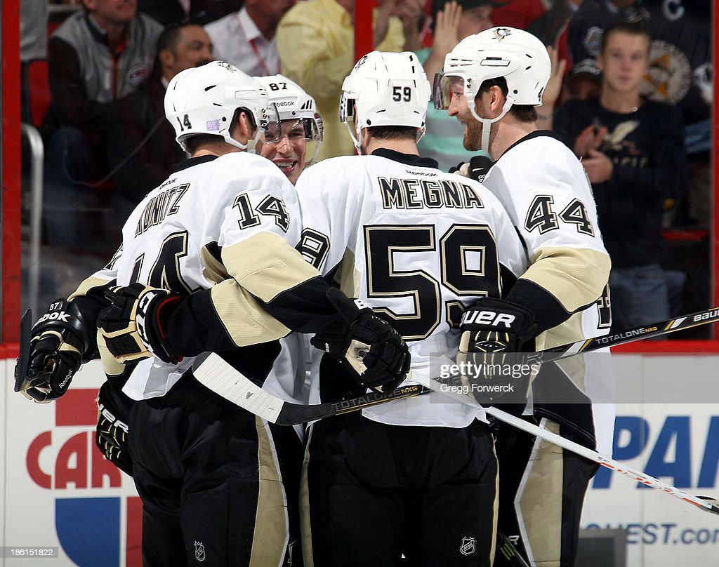 Chris Kunitz #14, Sidney Crosby #87 and Brooks Orpik #44 of the Pittsburgh Penguins celebrate a goal scored by Jayson Megna #59, his first NHL goal, against the Carolina Hurricanes at PNC Arena on October 28, 2013 in Raleigh, North Carolina.