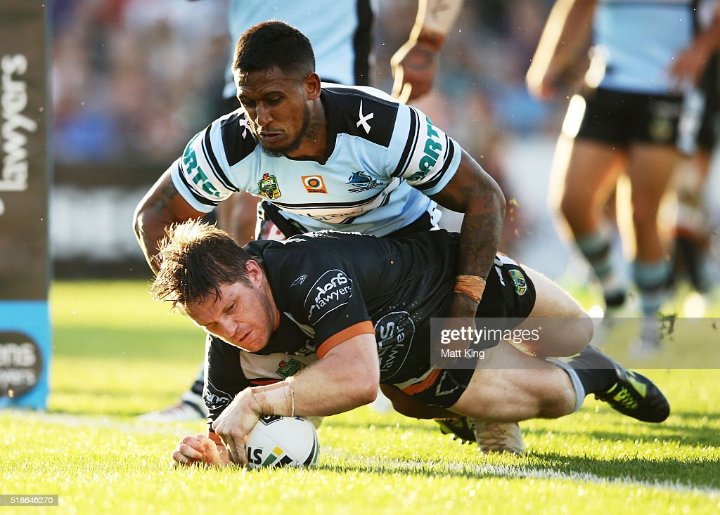 Chris Lawrence of the Tigers beats Ben Barba of the Sharks to score a try during the round five NRL match between the Wests Tigers and the Cronulla Sharks at Campbelltown Sports Stadium on April 2, 2016 in Sydney, Australia.