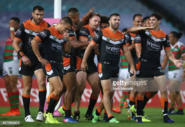 Chris Lawrence of the Tigers celebrates scoring a try with team mates during the round one NRL match between the South Sydney Rabbitohs and the Wests...