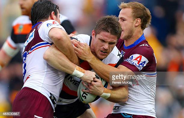 Chris Lawrence of the Tigers is tackled by Daly Cherry Evans and Jamie Lyon during the round five NRL match between the Wests Tigers and the...