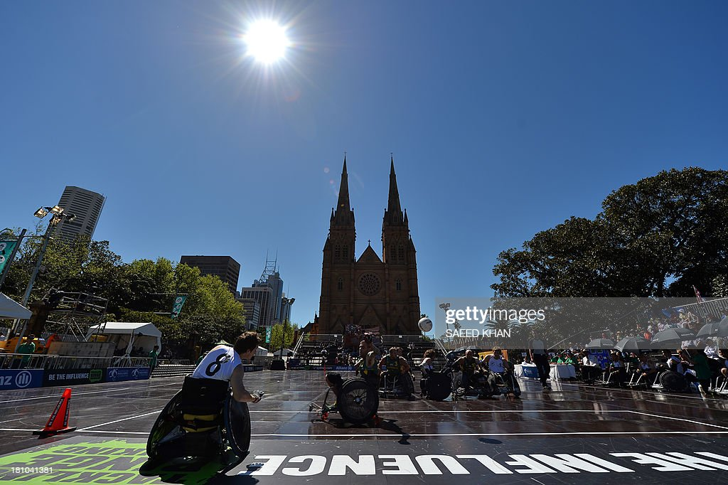 Chris Lay of New Zealand (L) passes to a teammate during their Wheelchair Rugby Tri-Nations match against Australia in front of St. Mary's Cathedral in Sydney on September 19, 2013. Wheelchair Rugby, which is also know as mederball due to its aggressive, full-contact nature, originated in Canada in 1977 and combines the elements of basketball, football and ice hockey. AFP PHOTO / Saeed KHAN USE